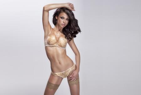 hot breast: Сексуальная брюнетка красивая женщина позирует в нижнем белье, глядя на камеру. Фото со стока
