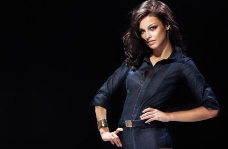 Beautiful brunette woman smiling, posing over dark background. Stock Photo - 21193765