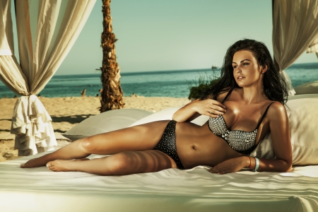 Young woman in swimsuit laying on chaise-longue at the beach in sunny day. Stock Photo - 21356197