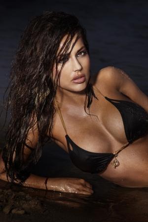 mojada: Retrato de preciosa joven morena se extiende en el mar, posando, mirando a la cámara.