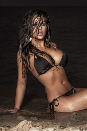 Sensual beautiful brunette woman posing on the beach at night. photo