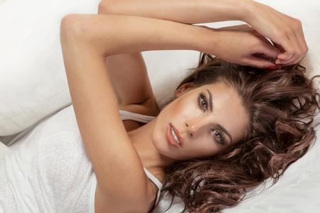 sensuous: Beautiful smiling young woman lying on her back in a bed, looking at camera. Stock Photo