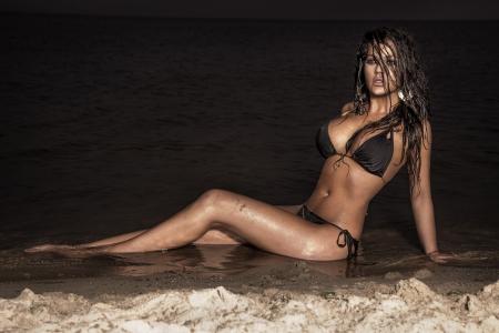tan woman: Beautiful, sexy brunette woman posing in swimwear on the beach at night. Perfect fitness body. Stock Photo