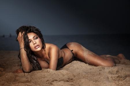 nue plage: Dame élégante avec un corps parfait pose à la plage. Soirée photo au coucher du soleil.