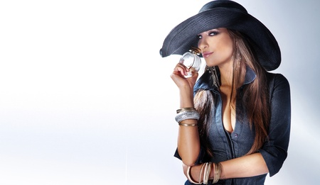 Portrait of beautiful young woman wearing hat, smelling perfume. photo