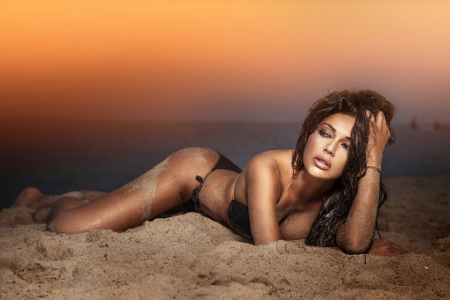 Elegant lady with perfect body laying at the beach. Evening photo during sunset.