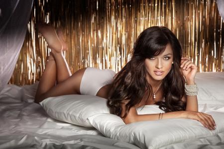 deitado: Foto sensual de mulher linda morena com cabelo encaracolado longo que levanta no quarto vestindo lingerie sexy branco. Imagens