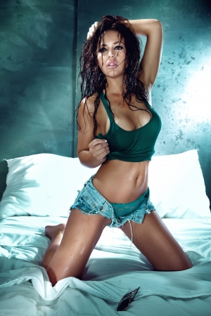 Photo of beautiful sexy brunette woman relaxing in bedroom.