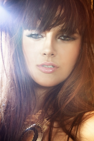 Portrait of beautiful young brunette woman with long hair, fringe and nice makeup, looking at camera. Stock Photo - 21889491