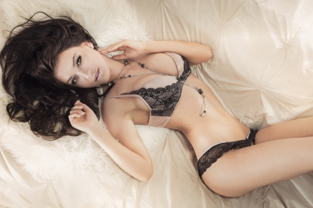 women breast: Sexy young brunette woman in lingerie lying, looking at camera. Stock Photo