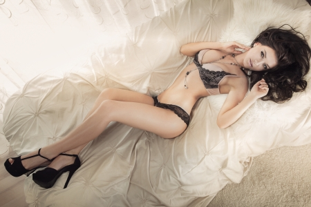 Photo of beautiful brunette woman looking at camera lying in sexy lingerie in big white bed and relaxing