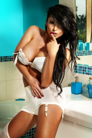 Sexy brunette woman with long hair posing in bathroom. Stock Photo