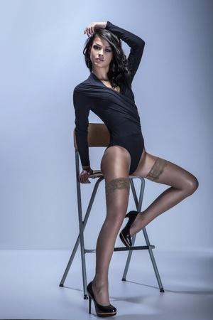 belles jambes: Portrait en pied de la belle brune jeune femme assise dans le corps à la mode et des chaussures noires
