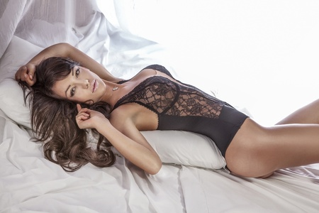 woman lingerie: Sensual brunette woman with long curly hair lying in white bed, posing in sexy black lingerie, looking at camera. Stock Photo