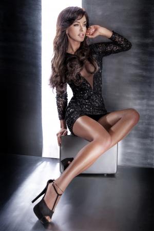 Fashion photo of beautiful lady in elegant evening dress sitting, looking away. photo