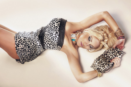 Elegant blonde woman lying on the floor, posing. photo