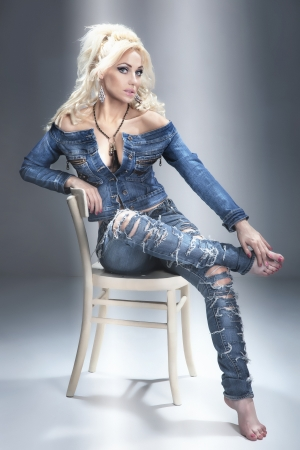 Beautiful blonde woman posing in jeans clothes, sitting, looking at camera. photo