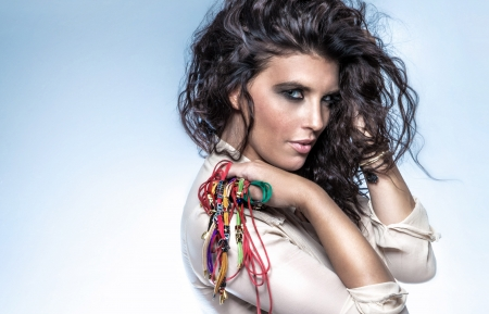 Portrait of beautiful young sensual woman with brunette curly hair and a lots of bracelets. photo