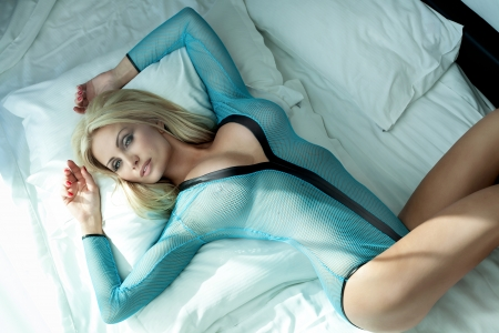 Beautiful blonde woman with long hair lying on white bed, posing, looking at camera  photo