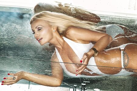 Attractive blonde woman taking shower in white swimsuit Stock Photo - 23331852
