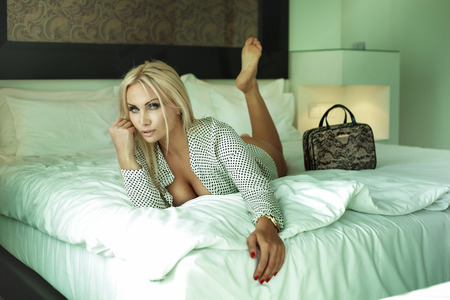 Beautiful blonde woman relaxing in hotel room, looking at camera  photo