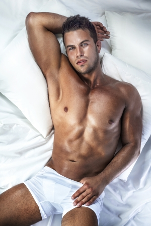 Handsome young man with perfect body lying in bed, looking at camera. Stock Photo