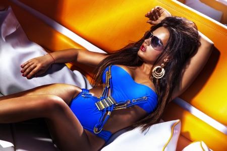 ni�as en bikini: Atractiva mujer morena tomando el sol en d�as de vacaciones.