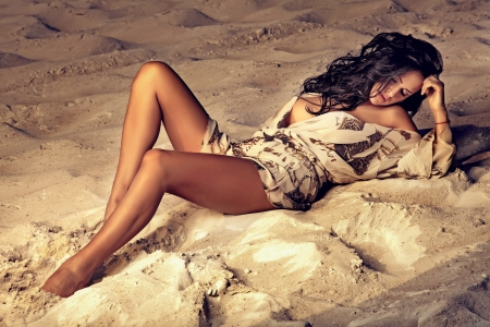 Sensual brunette lady posing at the evening on the beach