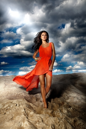 Fashionable young beautiful brunette woman posing in dress at the beach