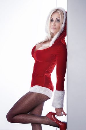 Sensual blonde woman posing in sexy mini dress in the style of Father Christmas