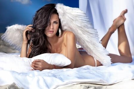 deitado: Anjo lindo deitado na cama grande branco, posando, olhando a c