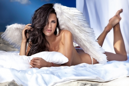 Beautiful angel lying in big white bed, posing, looking at camera