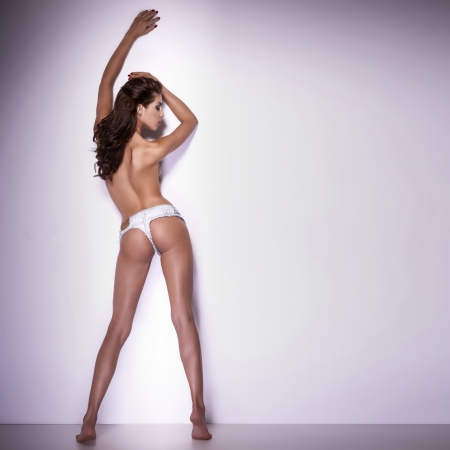 Sexy brunette woman posing over the wall