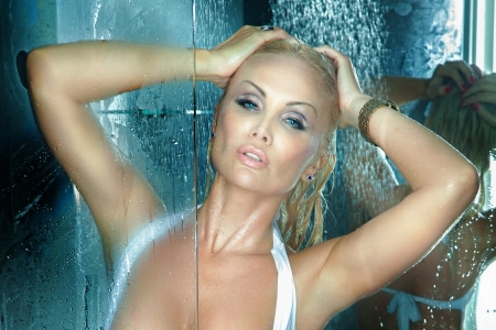 taking shower: Portrait of beautiful blonde woman taking shower, looking at camera. Stock Photo