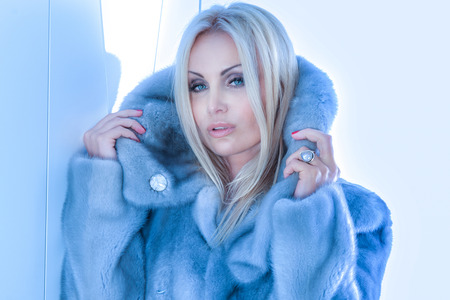Portrait of beautiful blonde woman wearing fur coat, looking at camera. photo
