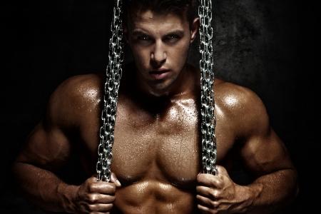 männchen: Gut aussehender junger Mann posiert mit Metallkette. Perfekte Körper.