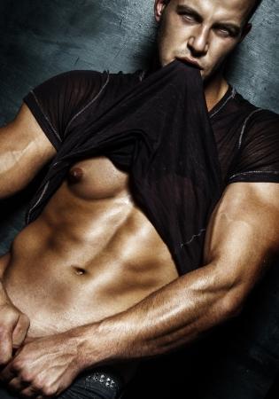 Very muscular handsome sexy guy posing on dark background.