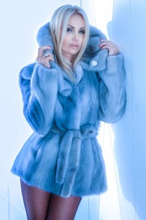 Modieuze blonde mooie vrouw poseren, het dragen van bont jas en kijken naar de camera. Stockfoto
