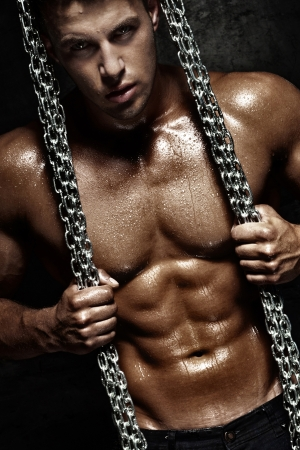 Handsome young man posing with metal chain, ideal bodybuilder.
