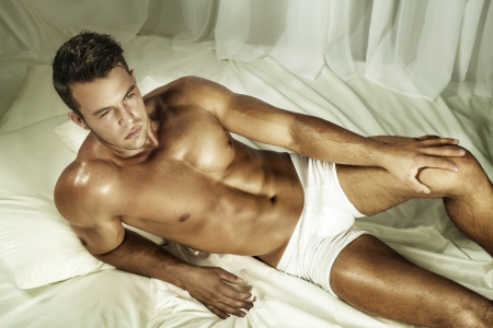 Handsome shirtless man lying in a bed. photo