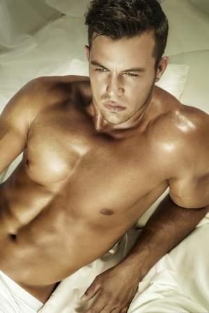 Portrait of handsome man lying shirtless on bed. Stock Photo