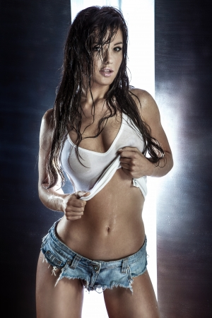 Young beautiful brunette woman posing in wet fashionable clothes and hair, looking at camera.
