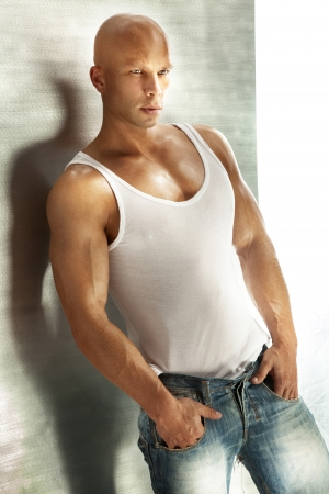 bald man: Hombre guapo cabeza calva posando en camiseta blanca y pantalones vaqueros.
