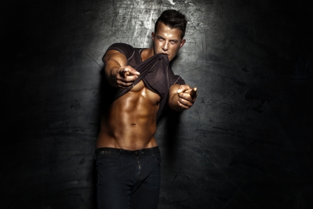 Very muscular handsome sexy guy posing on dark background.