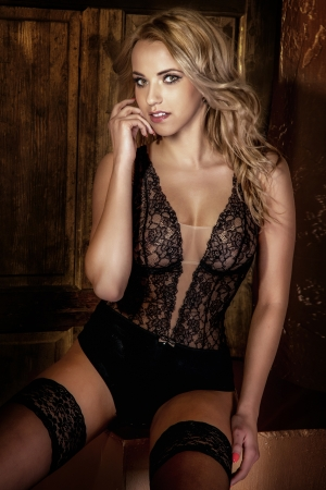 Beautiful blonde woman sitting wearing sexy lingerie, looking at camera.