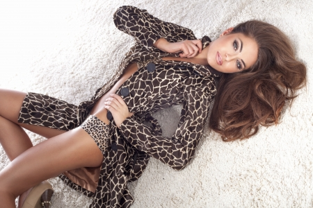 Sensual fashionable brunette woman lying on the fur, posing, looking at camera. photo