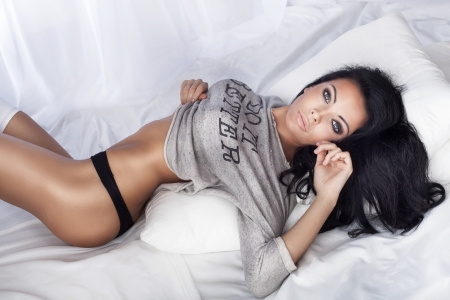 Beautiful brunette woman posing in white bed, looking at camera. photo