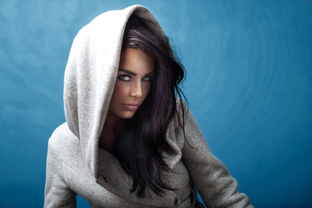 Sexy young brunette girl wearing a hood looking at camera.