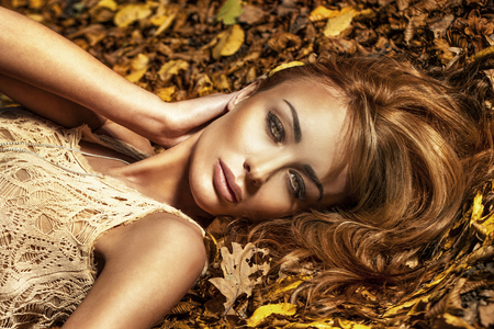 Portrait of beautiful young brunette woman with perfect makeup lying on leafs, looking at camera photo
