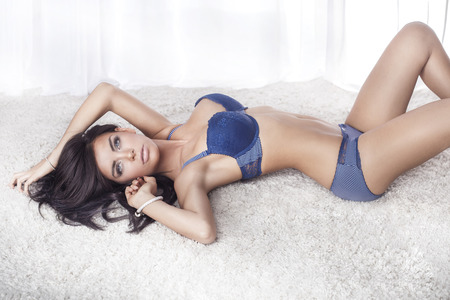 Sensual brunette woman with long hair lying in white bed, posing in sexy blue lingerie, looking at camera. photo